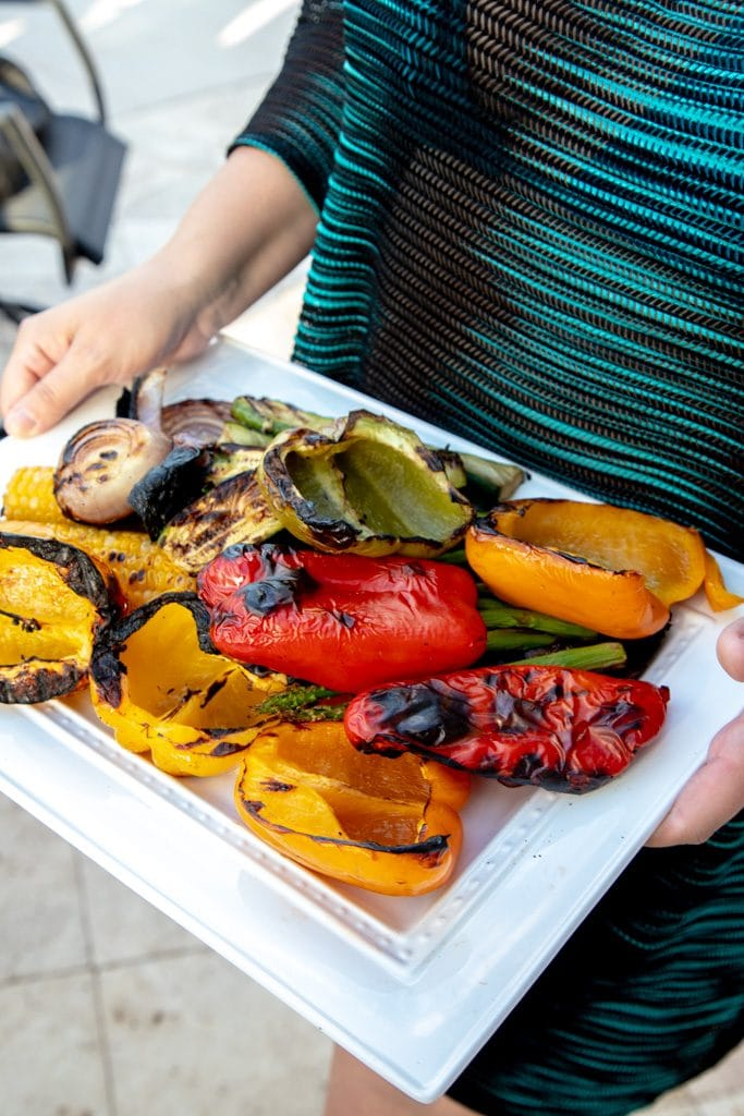 woman holding a white platter full of grilled vegetables
