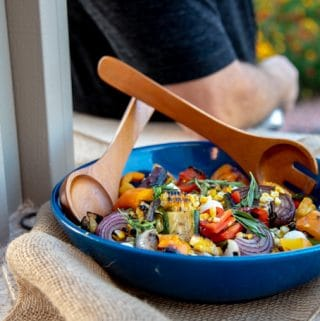 grilled vegetable salad in a blue bowl with wooden utensils