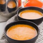 Roasted red pepper soup in black bowls, on newspaper