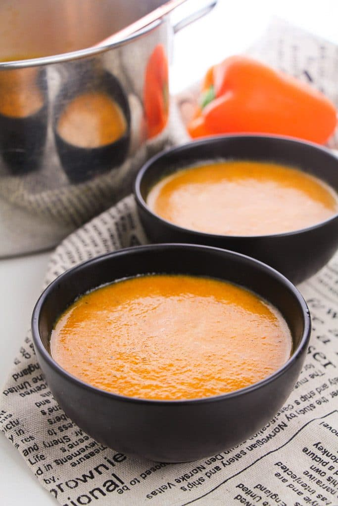 Roasted red pepper soup in black bowls with a red pepper in background