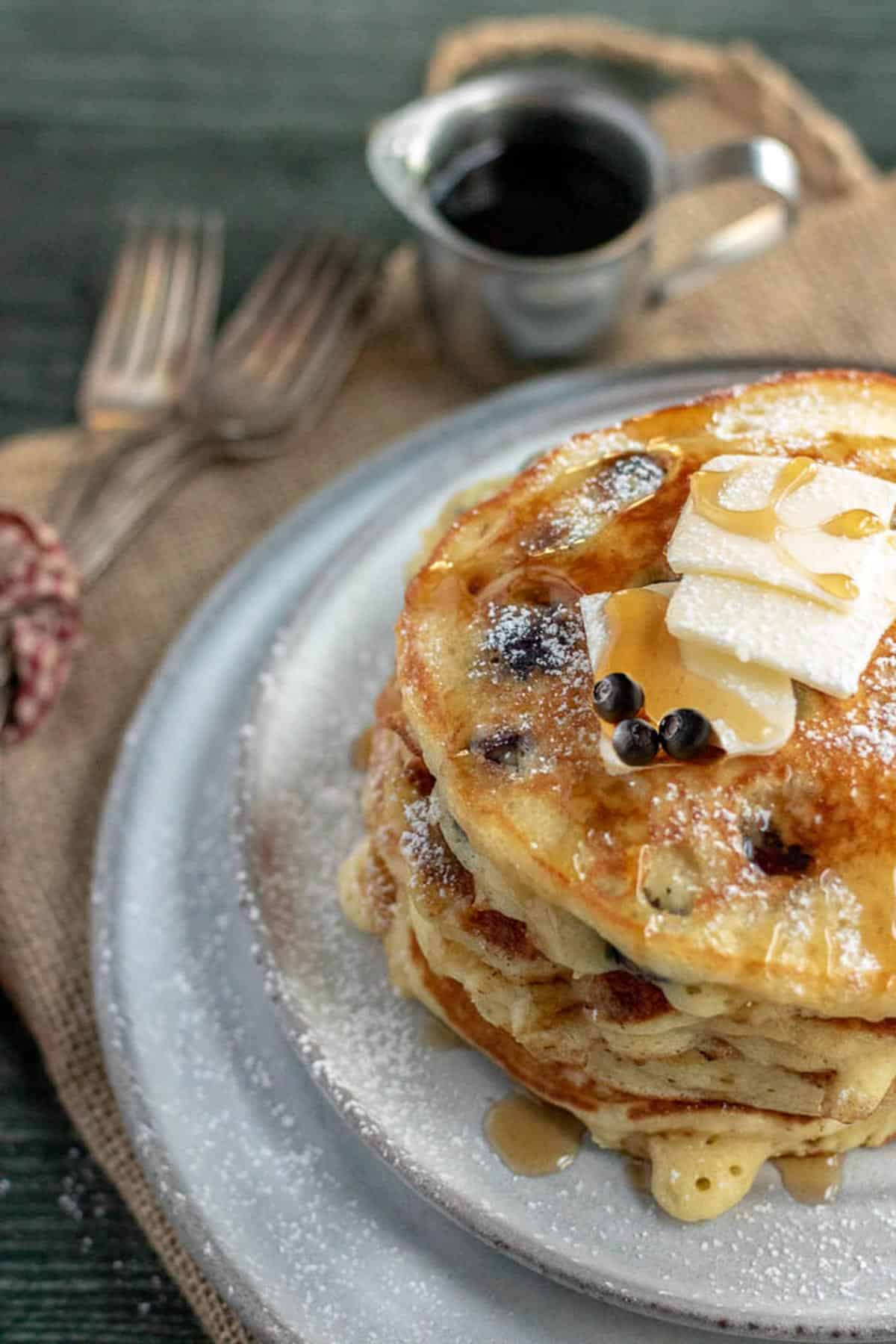 blueberry pancakes on a grey plate with forks and syrup