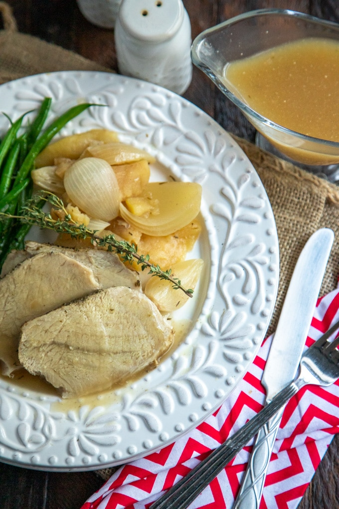 crock pot pork loin with green beans on a white plate with gravy