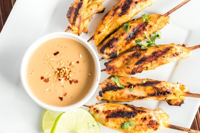 grilled chicken satay on a platter with peanut sauce and limes