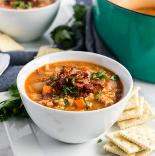 lentil soup in a white bowl with crackers