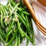 sauteed green beans on a white platter with wooden tongs