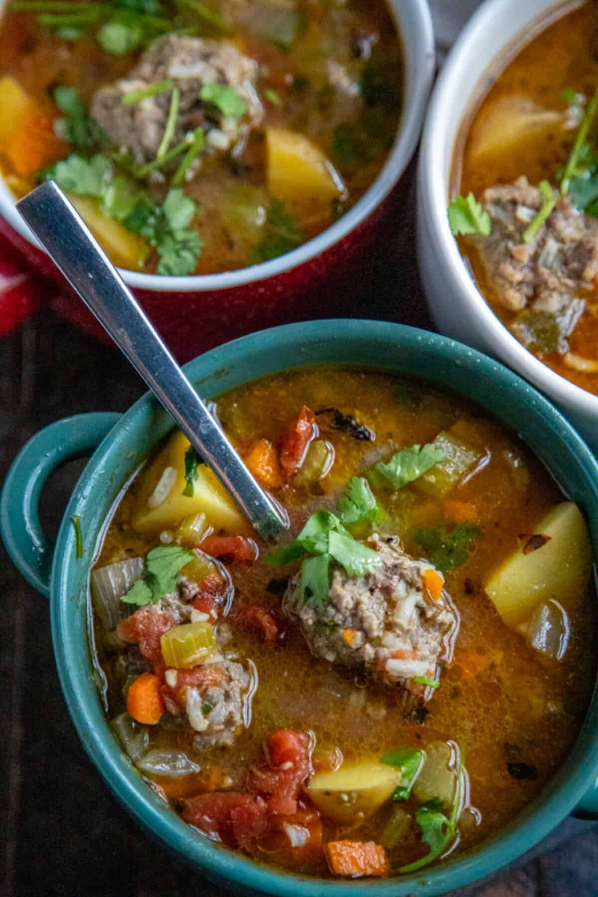 albondigas in teal bowls with a spoon