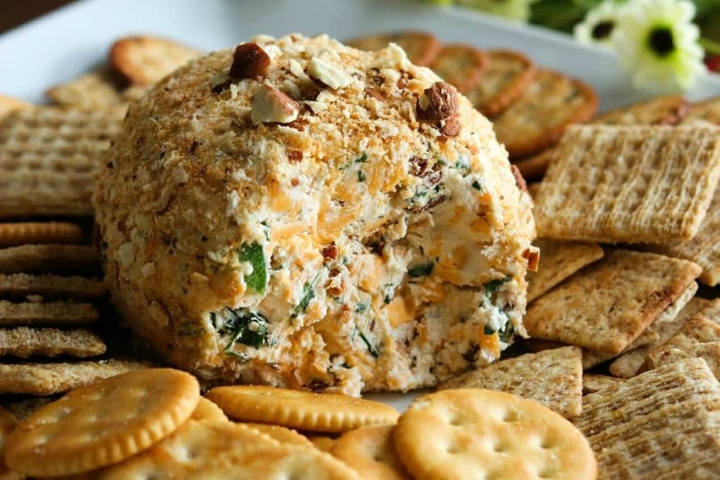Jalapeno Popper Cheese Ball surrounded by crackers on a white platter