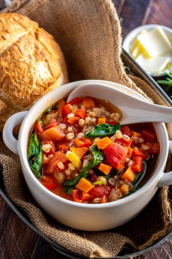 vegetable barley soup in a white bowl with a bread roll