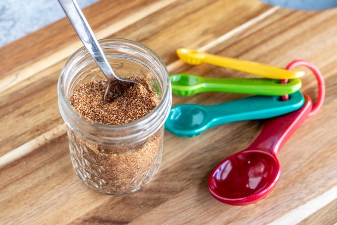 taco seasoning in a glass jar on a wooden cutting board with colored measuring spoons