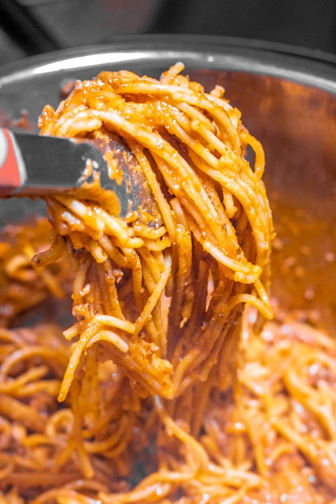 instant pot spaghetti in the pot, pulled out with tongs