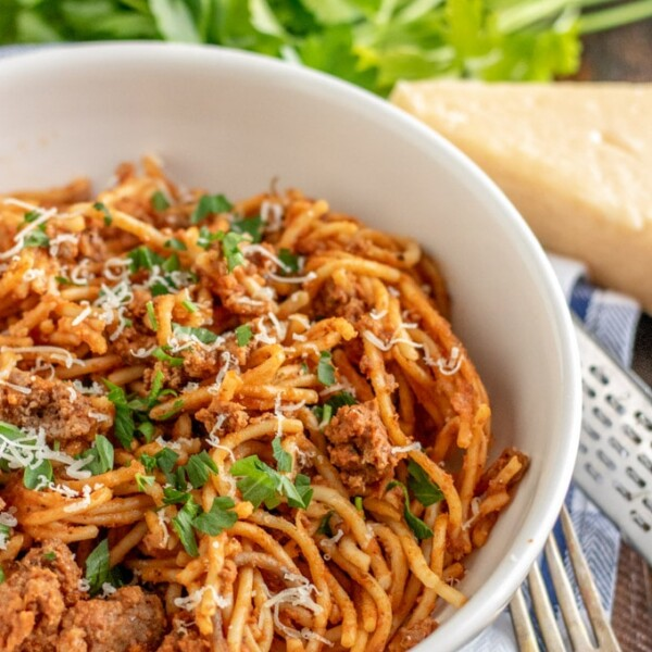 instant pot spaghetti in a white bowl with parsley and parmesan