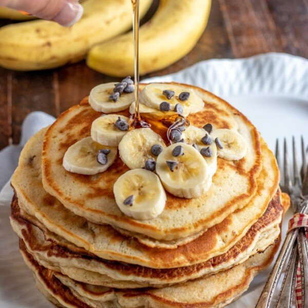 banana pancakes with syrup being poured over