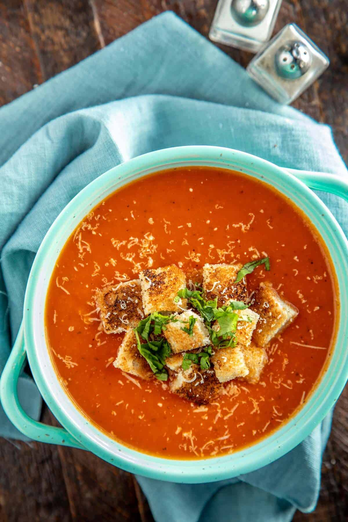 tomato soup in an aqua bowl with croutons