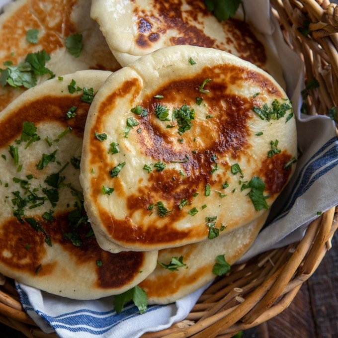 Naan bread in a basket lined with a kitchen towel