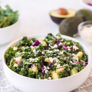 kale salad in a white bowl, with avocados in the background