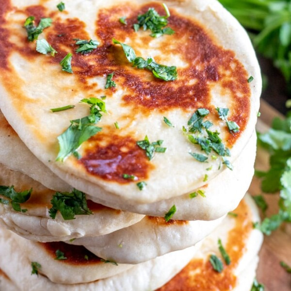 golden naan bread with cilantro stacked on a wooden board