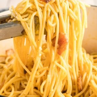 spaghetti carbonara being mixed with tongs