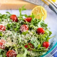 arugula salad in a bowl with lemon on the side