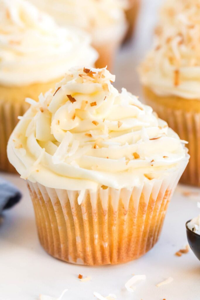 close up of a coconut cupcake with frosting and toasted coconut on top