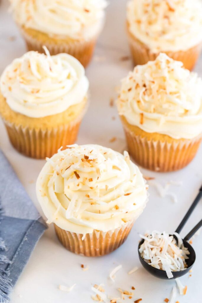 5 coconut cupcakes on a white background with toasted coconut in a spoon beside them