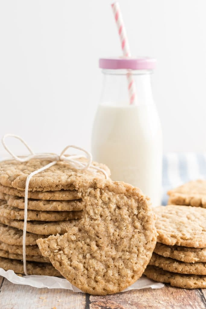 oatmeal cookies tied up with twine, with a bottle of milk in the background and a pink striped straw
