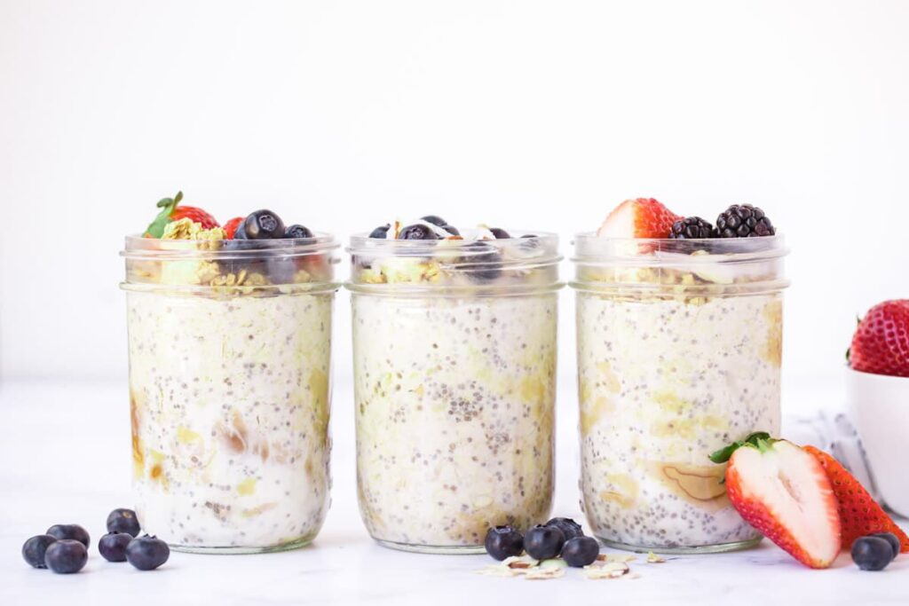 three jars of overnight oats in a row with berries
