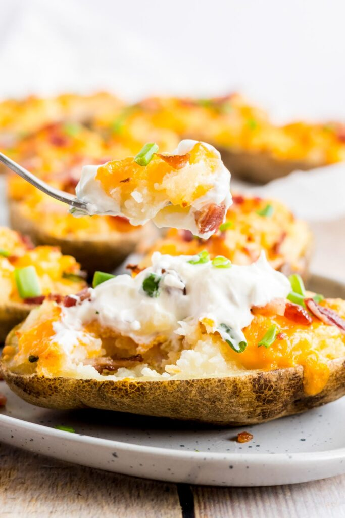 twice baked potatoes on a white plate, with a fork dug in pulling out the filling