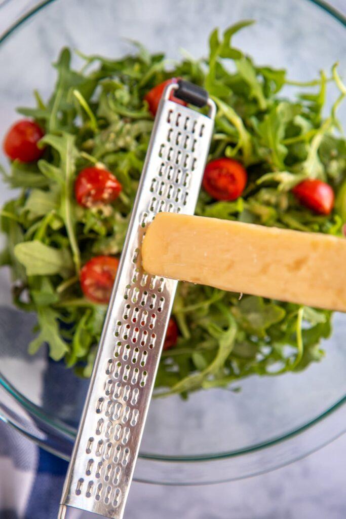 grating parmesan over a bowl of arugula salad