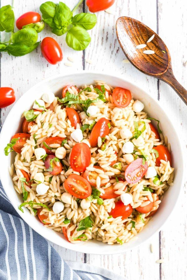 Caprese Orzo Salad in a white bowl with basil and tomatoes scattered around