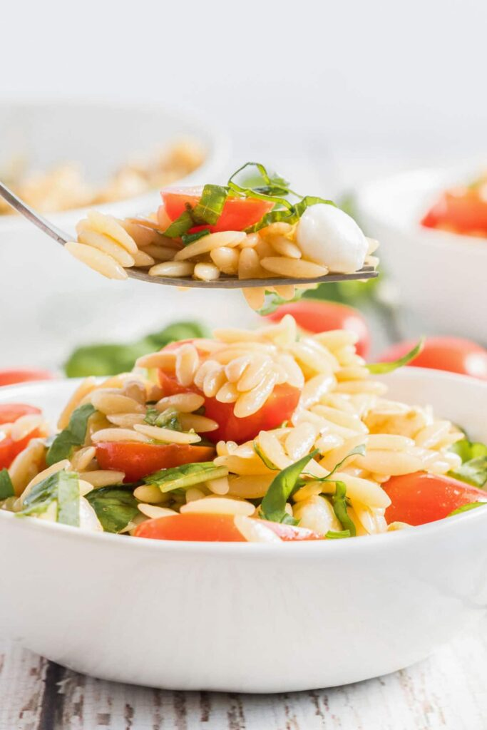 spoon full of Orzo Salad in a white bowl