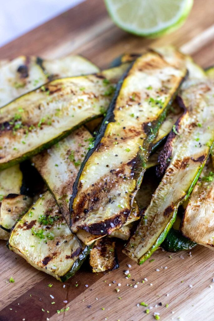 grilled zucchini on a chopping board with a lime