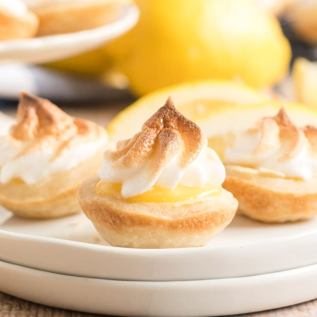 square image of mini lemon meringue pies on a white plate