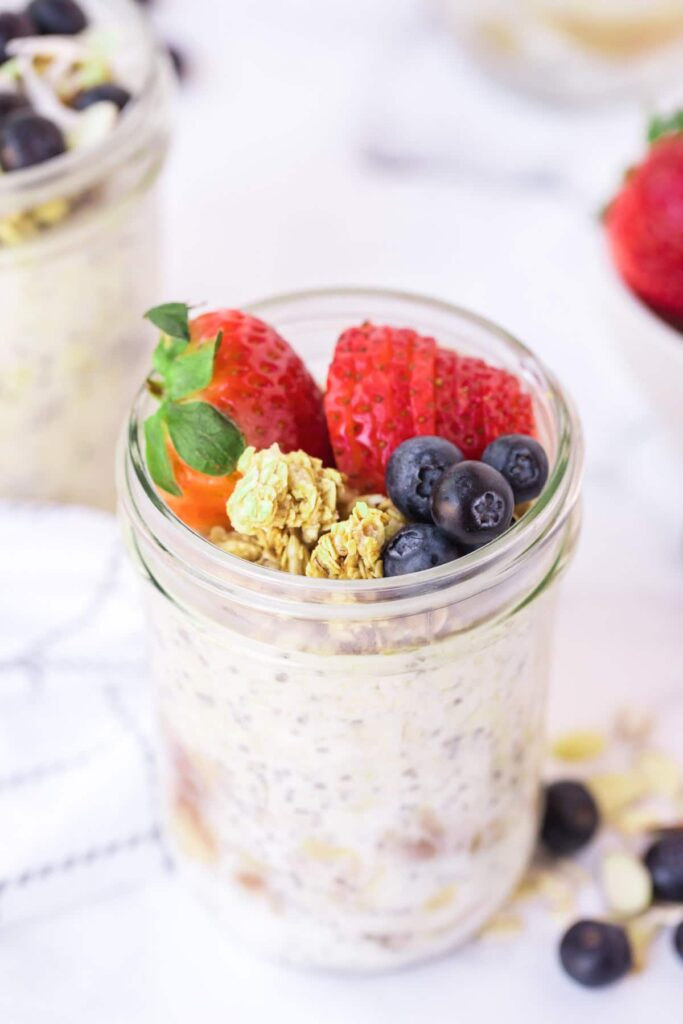 overnight oats with granola and berries on a marble backdrop