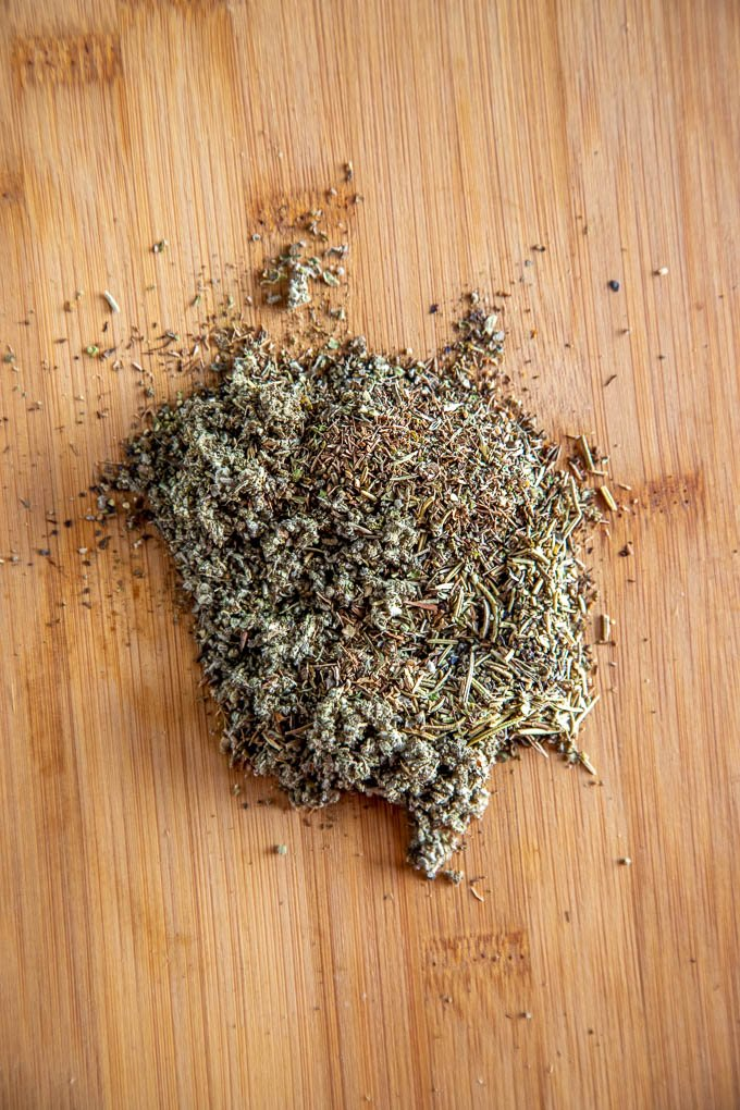 handful of dried herbs on a wooden board