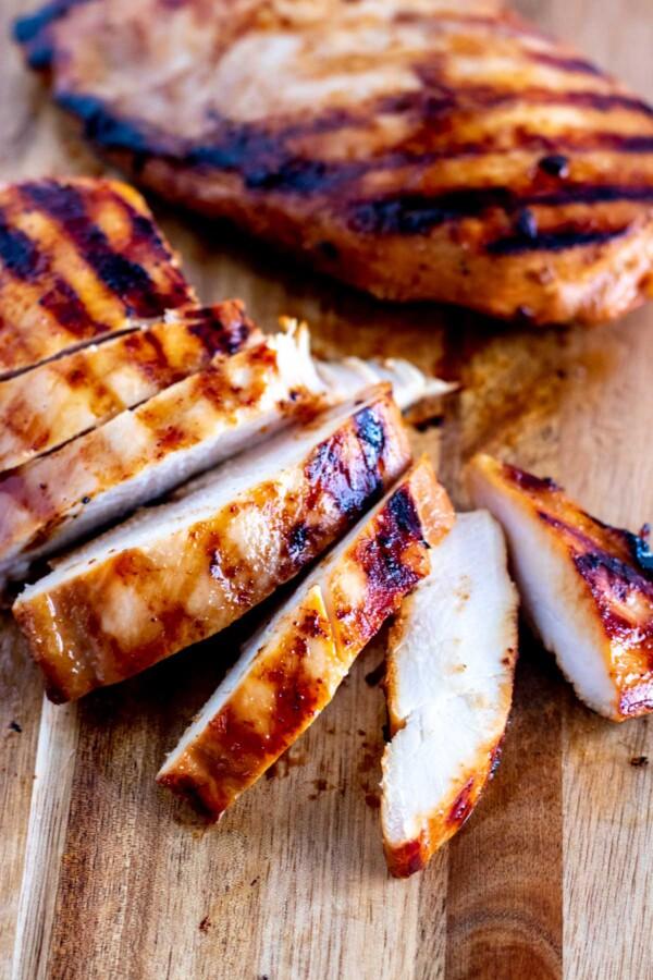 Grilled teriyaki chicken on a chopping board, sliced