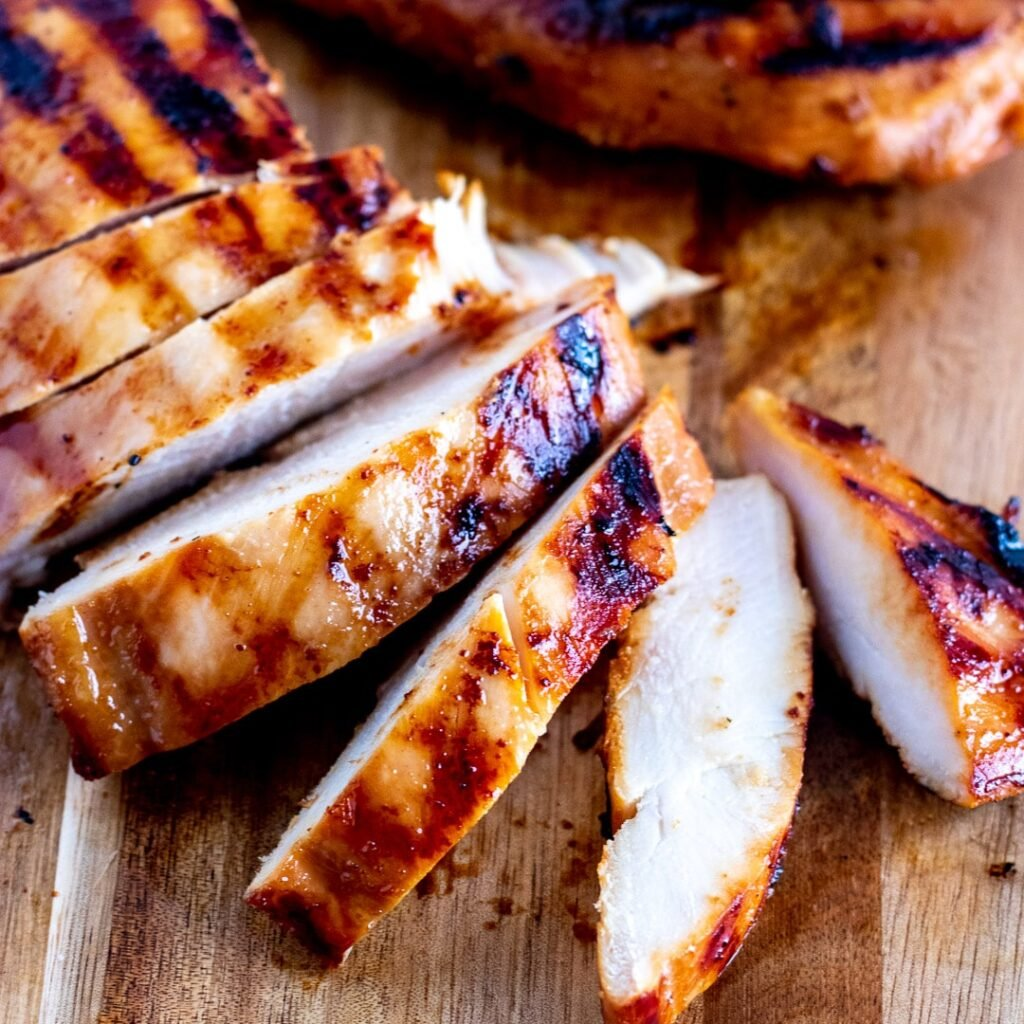 Grilled chicken on a chopping board, sliced