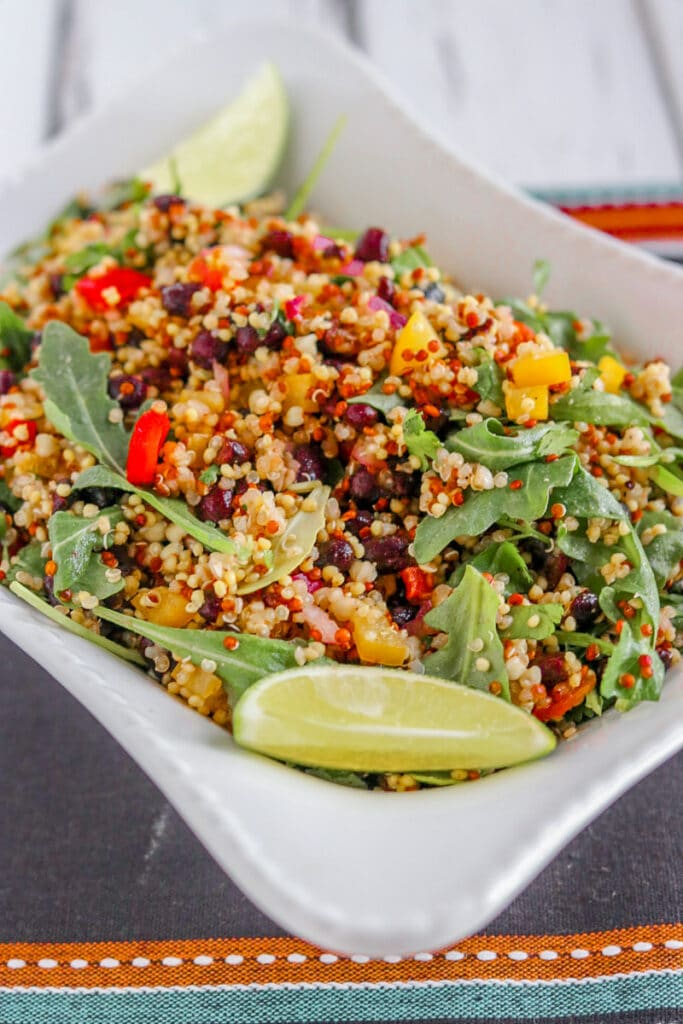 quinoa salad in a white bowl with a lime