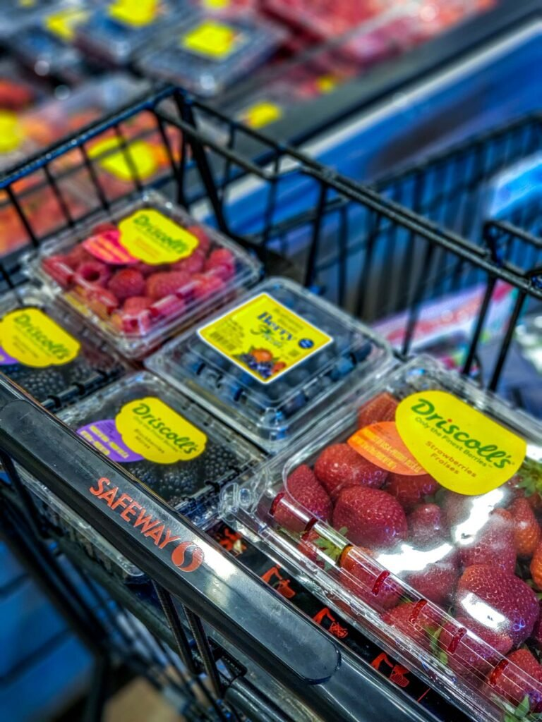 berries in packages in a grocery store cart