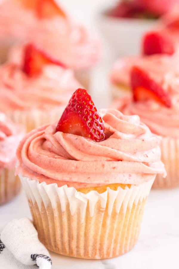 vanilla cupcake with pink frosting and a strawberry