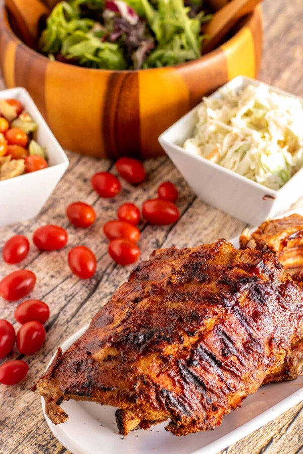 grilled ribs on a white plate with salads around