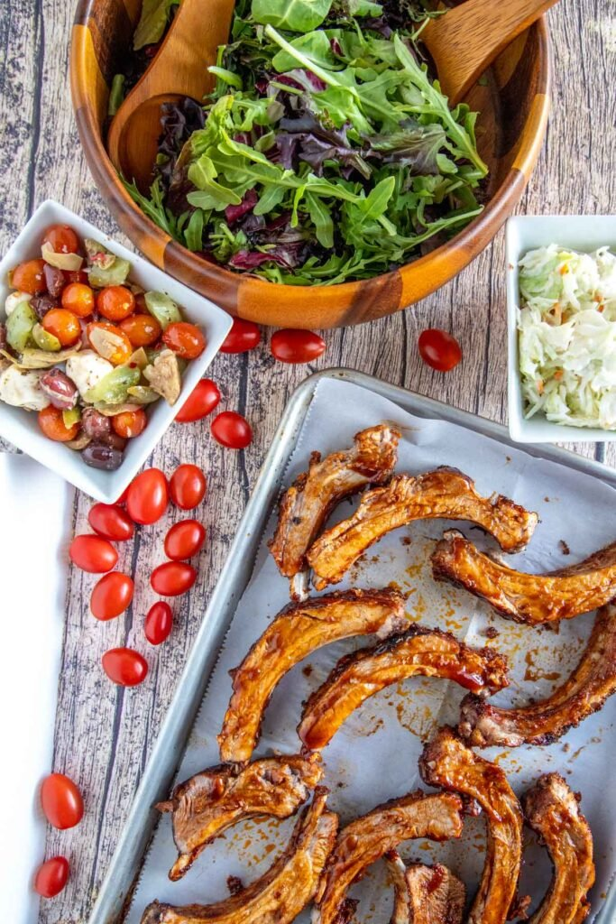 overhead shot of ribs on a baking sheet with salads