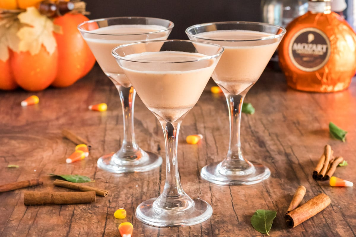 3 pumpkin martinis with cinnamon sticks
