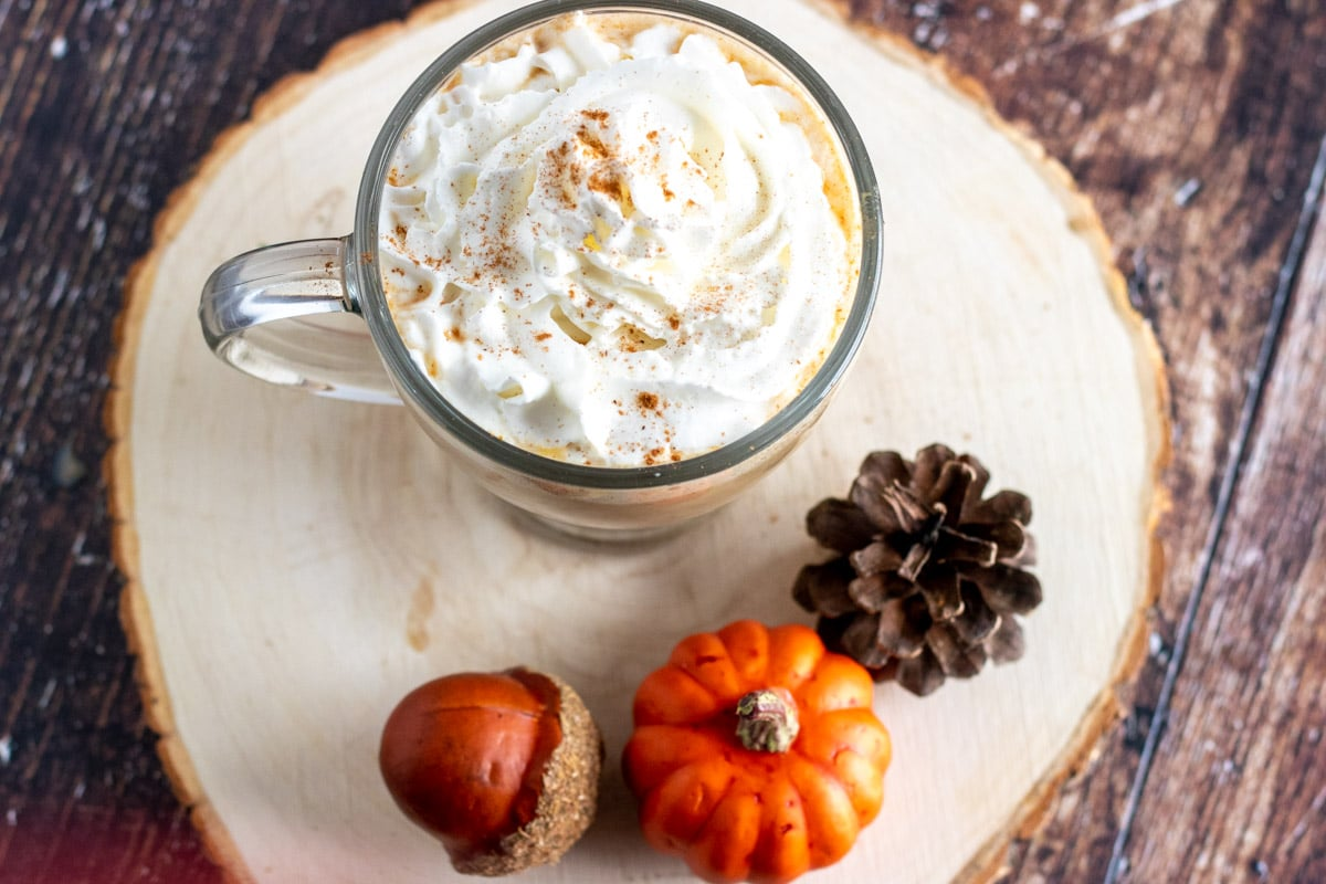 overhead shot of a cup of coffee topped with whipped cream, on a wood base with pumpkin decor