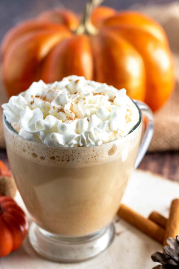 pumpkin spice latte with whipped cream in a clear mug