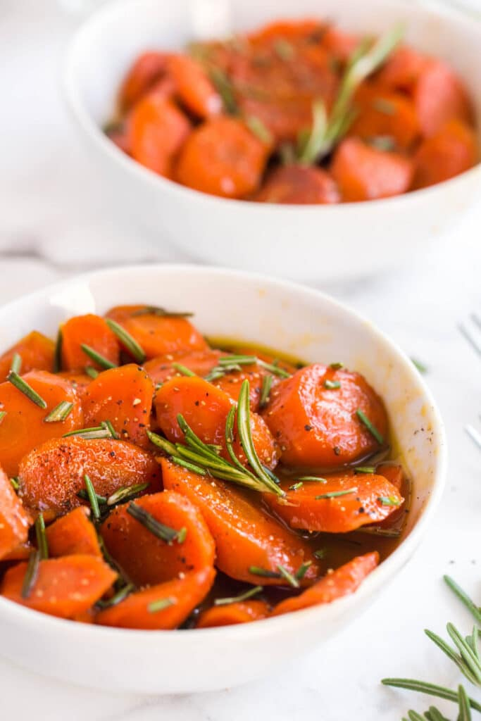 carrots with rosemary in two white bowls