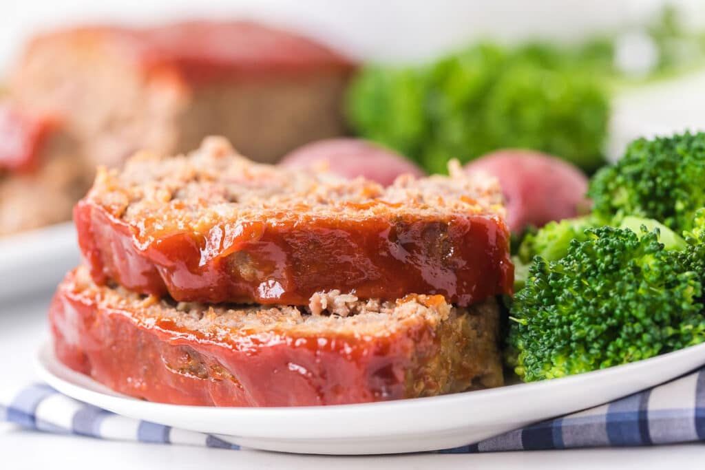 slices of meatloaf on a plate with steamed broccoli