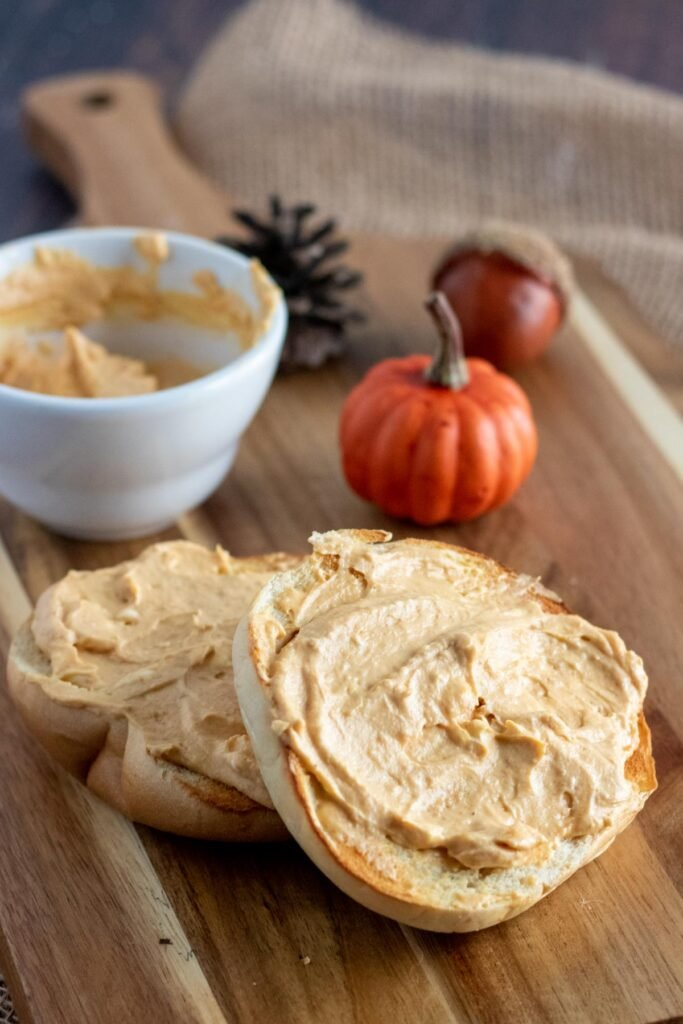 wooden board with a bagel schmeared with pumpkin cream cheese