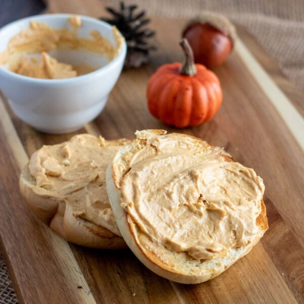 square image of a wooden board with a bagel schmeared with pumpkin cream cheese