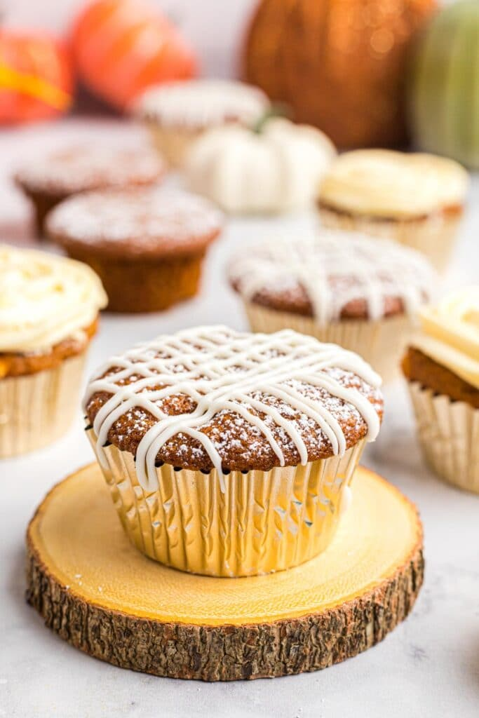 pumpkin muffin with white chocolate drizzled over the top, in a gold foil liner