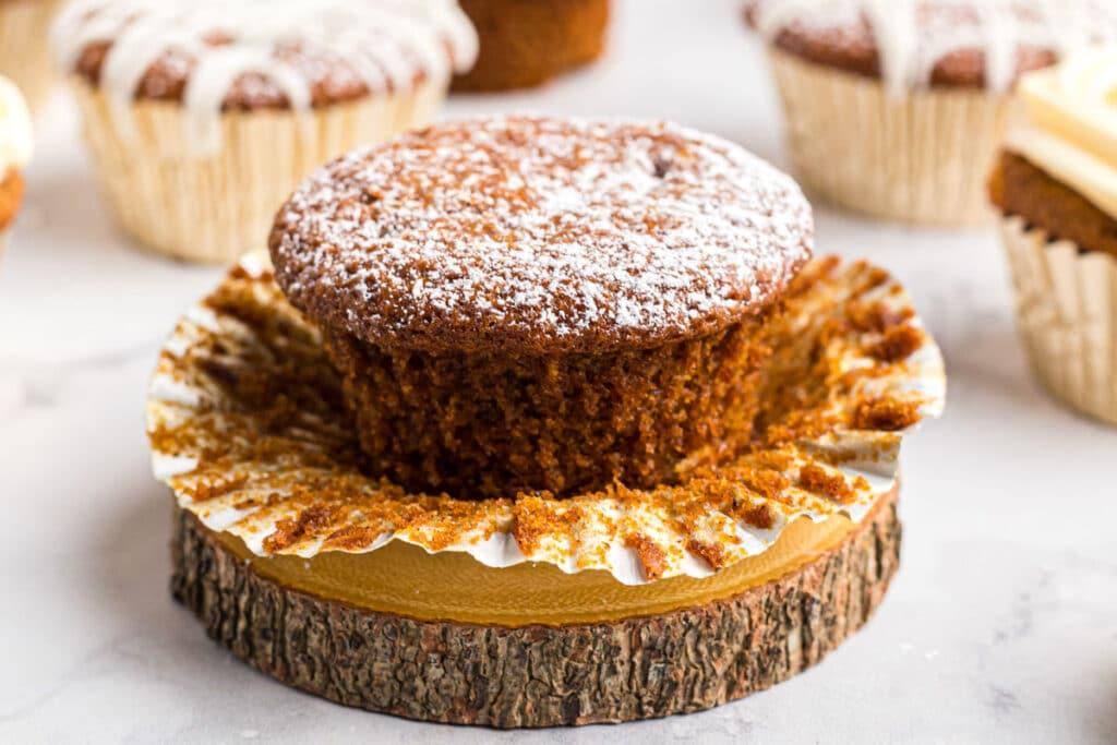 cupcake with powdered sugar on a wood log